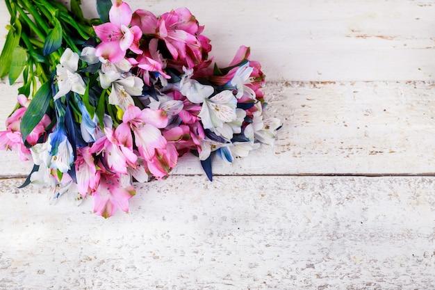 Mooi boeket van roze en blauwe alstroemeria's op witte houten ondergrond.