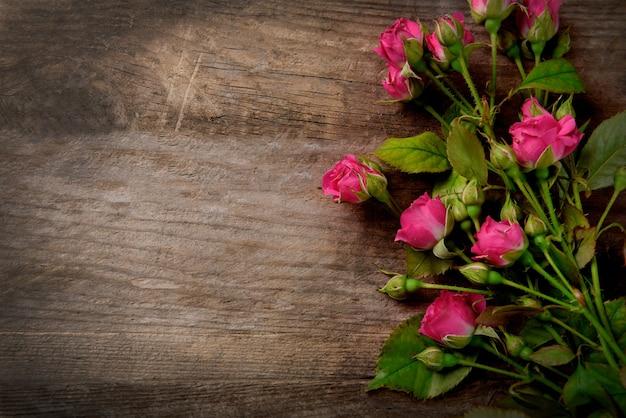 Mooi boeket van roze kleine rozen op houten, kopieer ruimte