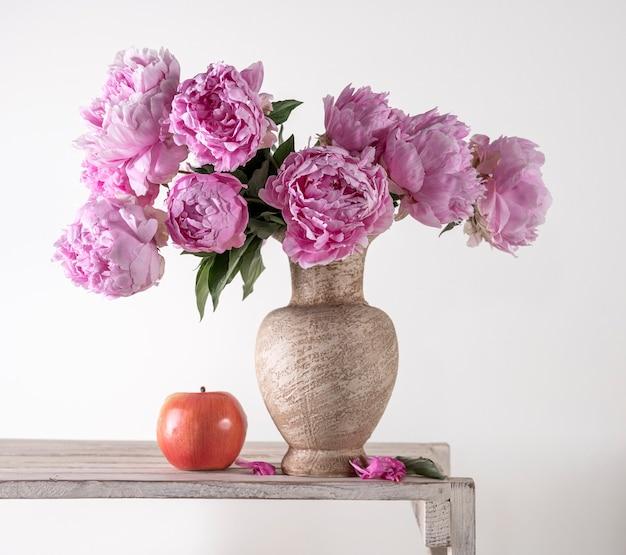 Mooi boeket van roze pioenrozen in vaas en appel op een grijze achtergrond