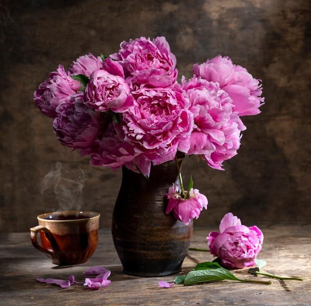 Mooi boeket van roze pioenrozen in vaas en kopje hete thee op een houten tafel