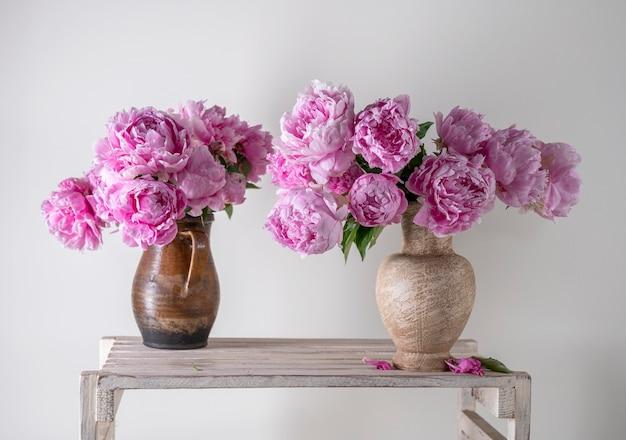 Mooi boeket van roze pioenrozen in vaas op een grijze achtergrond
