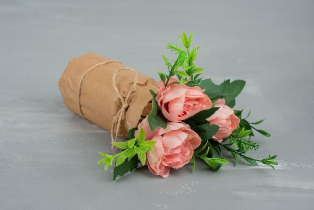 Mooi boeket van roze rozen op grijze tafel.