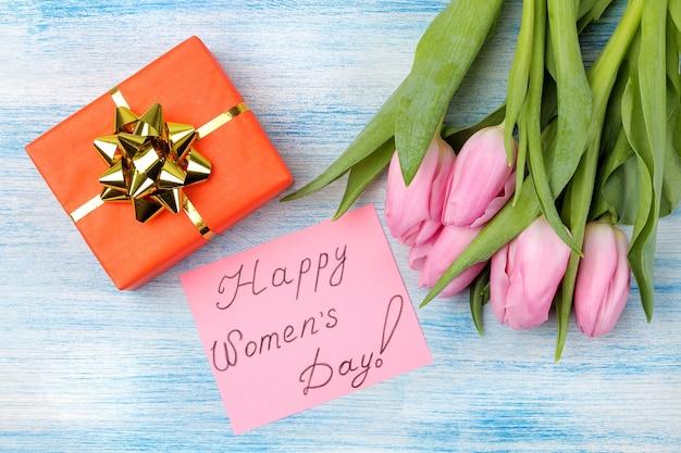 Mooi boeket van roze tulpenbloemen, geschenkdoos en tekst happy women's day op papier op blauwe houten ondergrond