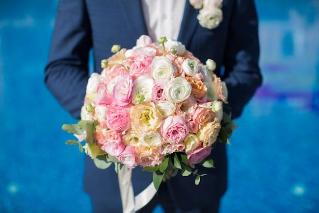 Mooi boeket van verse bloemen in de handen van de bruidegom op het zwembad bij het hotel