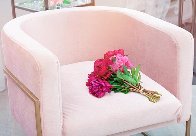 Mooi boeket van verse pioenbloemen op een lichtroze stoel