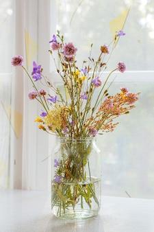 Mooi boeket van wilde bloemen tegen de achtergrond van een raam in een houten huis