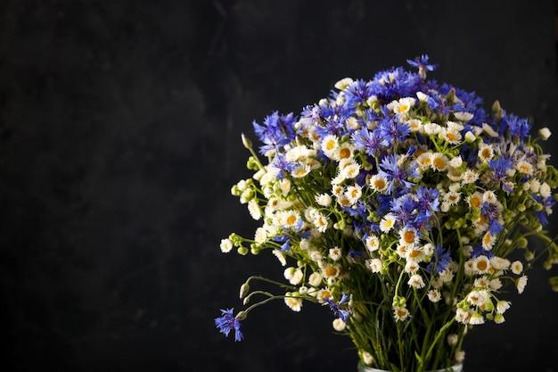 Mooi boeket van wilde bloemen voloshki en chamomiles op een donkere achtergrond