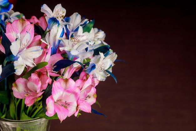 Mooi boeket van witte, roze en blauwe alstroemeria's op een donkere ondergrond. detailopname.