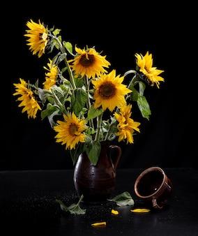 Mooi boeket van zonnebloemen in vaas en kopje thee op een zwarte tafel