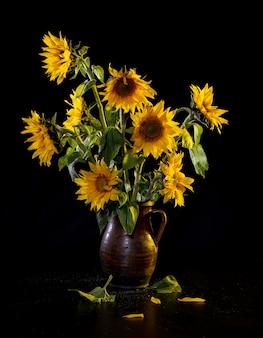 Mooi boeket van zonnebloemen in vaas op een zwarte tafel