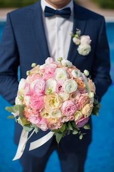 Mooi boeket verse bloemen in de handen van de bruidegom op de achtergrond van het zwembad van het hotel