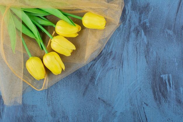 Mooi boeket verse gele tulpen op blauw.