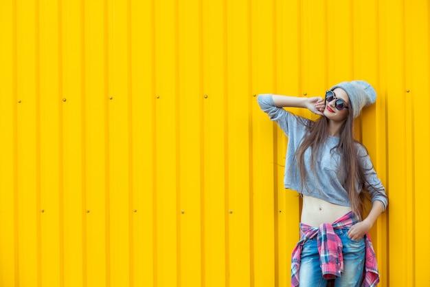 Mooi bool-meisje over gele muur