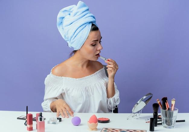 Mooi boos meisje gewikkeld haar handdoek zit aan tafel met make-up tools houden en toepassen van lippenstift spiegel geïsoleerd op paarse muur kijken