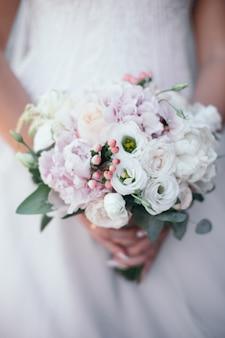 Mooi bruidsboeket met rode, roze en witte bloemen, rozen en eucalyptus, pioenrozen, calla lelies