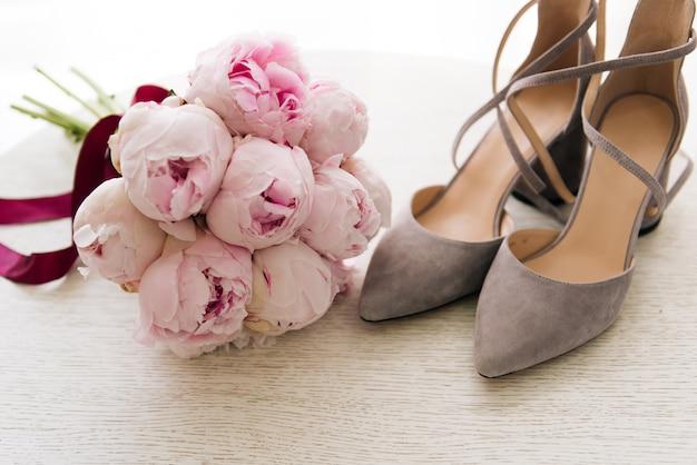 Mooi bruidsboeket van roze pioenrozen naast de schoenen van de bruid