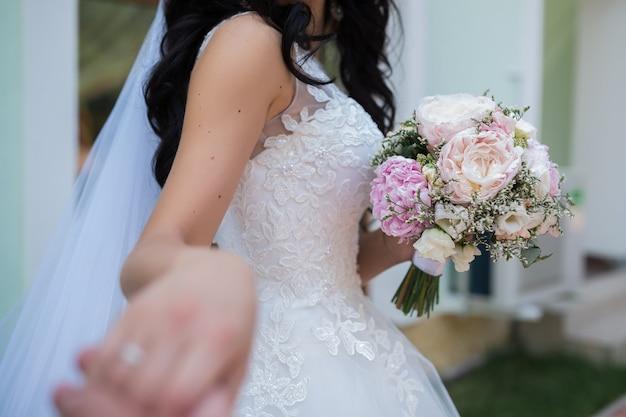 Mooi bruidsboeket van verschillende bloemen in de handen van de bruid