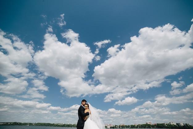 Mooi bruidspaar op de achtergrond van blauwe lucht, water