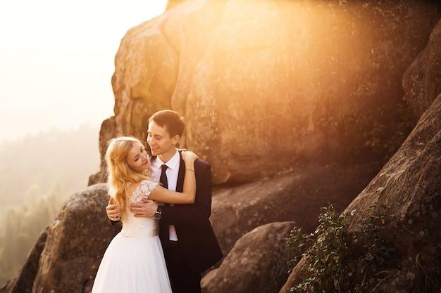 Mooi bruidspaar zacht knuffelen met de zon op hen