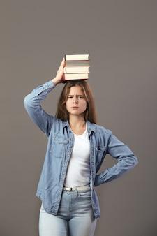 Mooi bruinharig meisje gekleed in een wit t-shirt, jeans en jeans houdt boeken op haar hoofd op een grijze achtergrond.