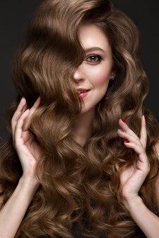 Mooi bruinharig meisje met perfect krullend haar en klassieke make-up