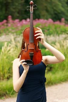 Mooi bruinharig meisje van aziatische verschijning met een viool in de natuur. muzikant in de natuur. klassieke muziek. hoge kwaliteit foto