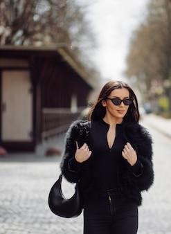 Mooi bruinharige stijlvolle meisje in zwarte jurk buiten. jonge aantrekkelijke elegante vrouw portret met lang haar op de lente in stadsstraten.