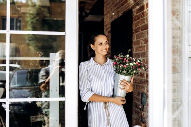 Mooi brunette meisje gekleed in een gestreepte jurk houdt een vaas met roze en witte chrysanten buiten bij de deur.