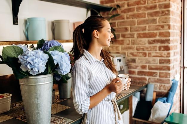 Mooi brunette meisje gekleed in een gestreepte jurk staat in de bloemenwinkel in de buurt van de vaas met lichtblauwe hortensia en houdt een kopje vast.
