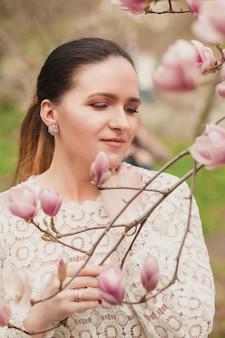 Mooi brunette model met naakte make-up, kanten blouse dragend, poserend in de buurt van de bloeiende magnoliabloemen