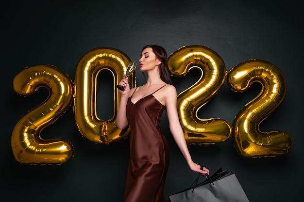 Mooi brunette model staat op een donkere achtergrond met luchtballonnen letters en houdt glas c...