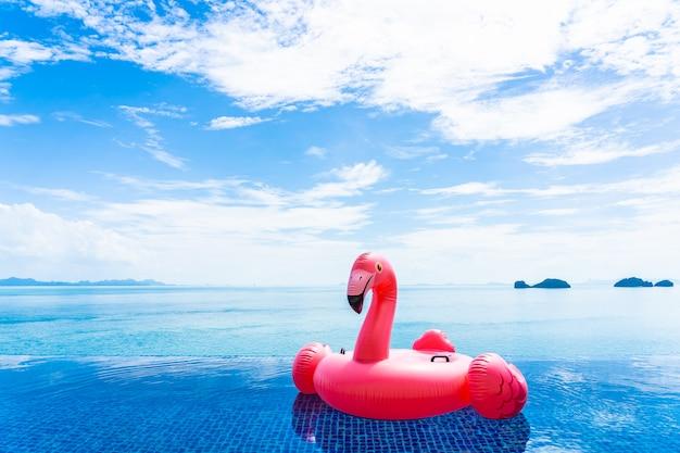 Mooi buitenzwembad in hoteltoevlucht met flamingovlotter rond overzeese oceaan witte wolk op blauwe hemel