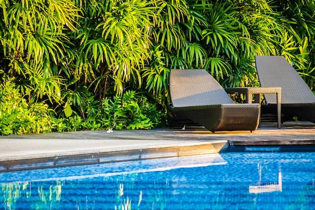 Mooi buitenzwembad met ligstoel en parasol in resort voor reizen en vakantie