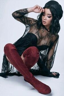 Mooi charmant aziatisch meisje in zwarte lange jurk en lederen hoed