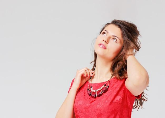Mooi charmant donkerbruin meisje in rode kledingshand die de n houden
