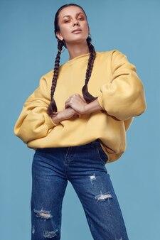 Mooi charmant spaans meisje in jeans en gele hoody