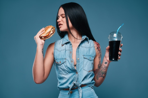 Mooi charmant tattoo-meisje met hamburger en frisdrank