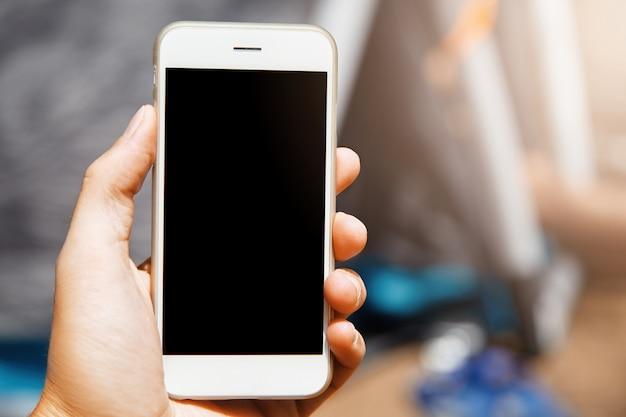Mooi close-up shot van moderne gadget in de hand. mooie telefoon met een laconiek ontwerp is een superhandig apparaat in het moderne tijdperk van geavanceerde technologieën met alle gebruikte mobiele applicaties.