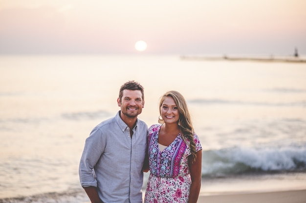 Mooi close-upportret van een jong paar dat voor een overweldigend zeegezicht stelt