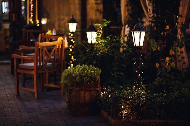 Mooi decor van lantaarns en slingers buiten in het tuincafé.
