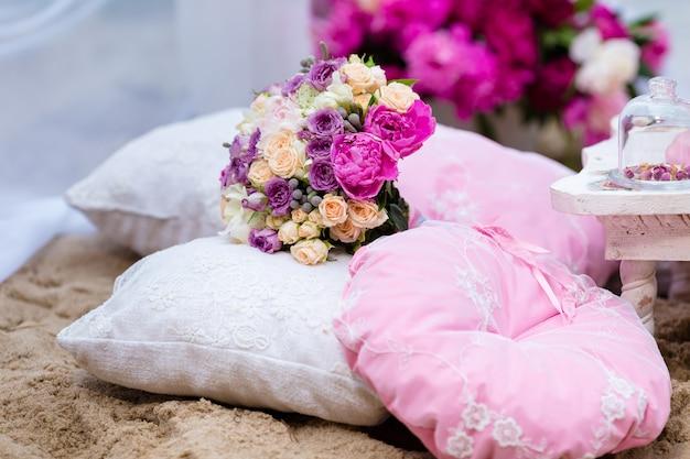 Mooi, delicaat bruidsboeket onder decoraties met kussen