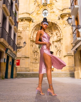 Mooi dominicaanse etnische meisje met vlechten met een mooie roze jurk. mode genieten van de zomer in een prachtige kerk van de stad