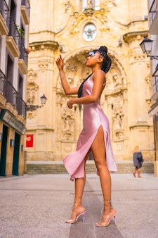 Mooi dominicaanse etnische meisje met vlechten met een mooie roze jurk. mode genieten van de zomer in een prachtige stadskerk, verticale foto