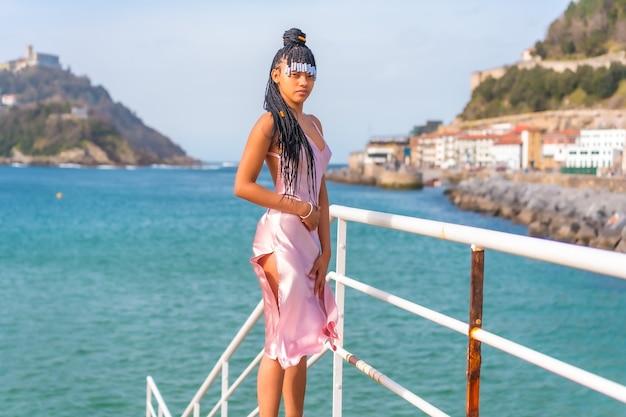 Mooi dominicaanse etnische meisje met vlechten met een mooie roze jurk. mode genieten van de zomer op een houten loopbrug aan zee