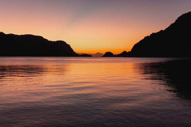 Mooi donker zeegezicht bij zonsondergang