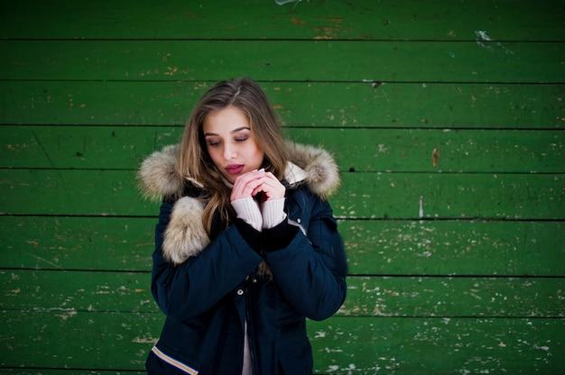 Mooi donkerbruin meisje in de winter warme kleding. model op de winterjas tegen groene houten achtergrond.
