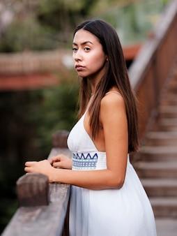 Mooi donkerbruin meisje in een witte kleding die weg de aard bekijken