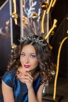 Mooi donkerbruin meisje met een gouden kroon, oorbellen en professionele avond make-up. meisjesmodel kaukasisch met prachtig kapsel en make-up met unieke kroon in de mode jurk met kettingen