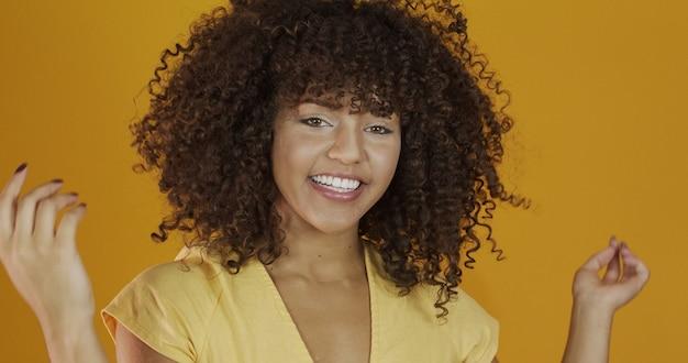 Mooi donkerbruin model dat bij camera glimlacht. mooie tanden. gekruld haar. braziliaanse jonge vrouw.