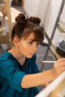 Mooi donkerharig schoolmeisje dat zich betrokken voelt bij het schilderen